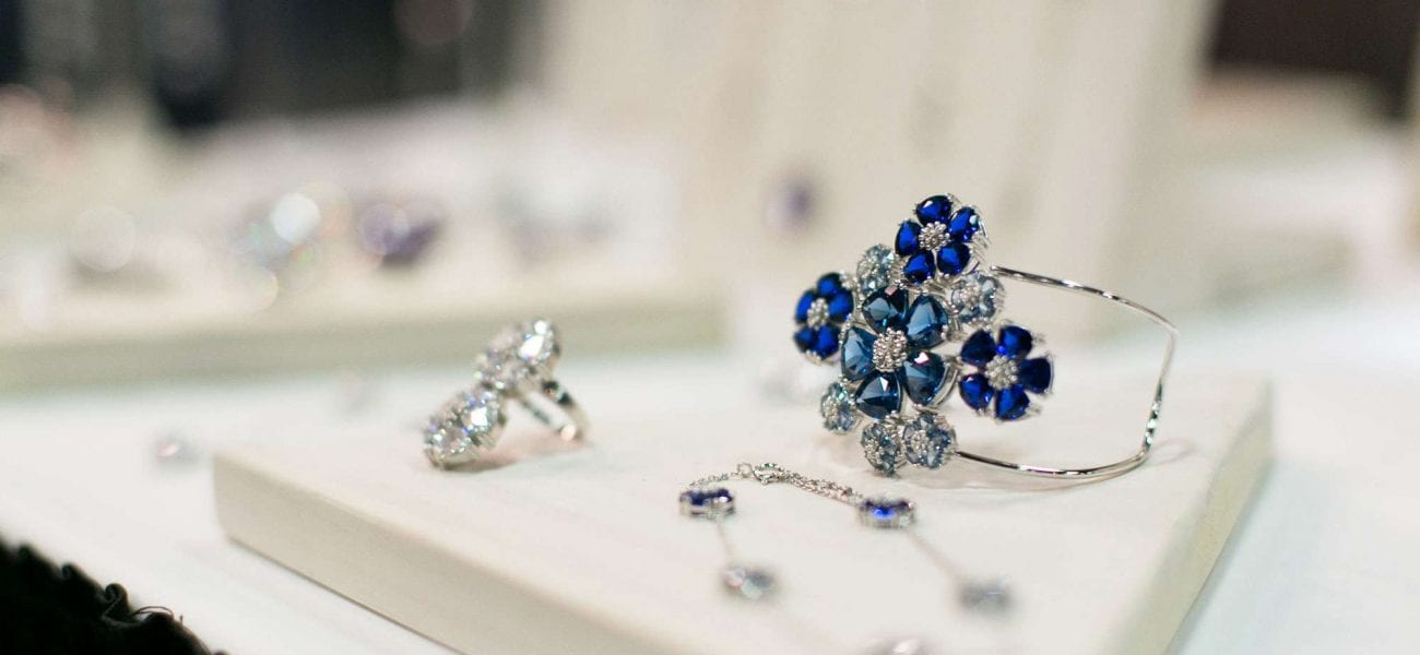 A woman's silver bracelet with blue gemstone flowers
