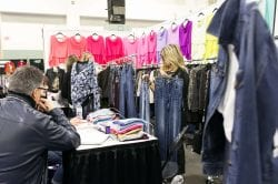 woman holding up two pairs of jeans in her apparel booth
