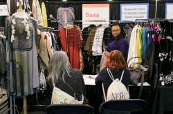 two women sitting and listening to another woman in a rep's apparel booth