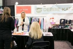 women talking at a clothing and accessory booth