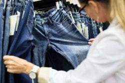 a woman sorting through a rack of jeans