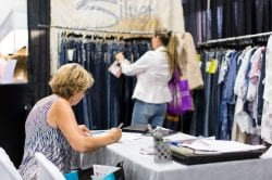 a buyer taking notes at the new england apparel company trade show in marlboro, ma