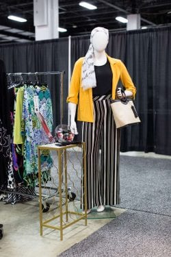 a mannequin wearing striped pants and a yellow jacket wearing a head scarf