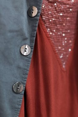 a close-up of jacket buttons and a red sequined shirt