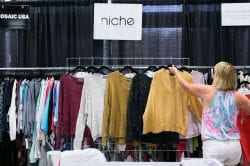 A rep at the niche trade show booth hanging a yellow sweater on a clothing rack