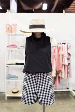 a mannequin wearing a black shirt, checked shorts and a straw hat