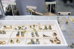 a tray of gold jewelry with green gemstones