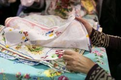 a woman's hands sorting through floral patterned fabrics