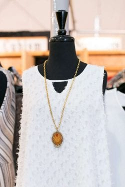a white textured sleeveless dress on a mannequin wearing a long gold necklace