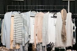 blue, pink and white pastel sweaters on a display rack