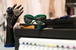 mannequin hand with two large rings and a pair of green sunglasses