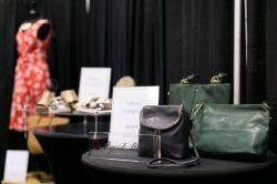 a table of leather purses with a red dress in the background