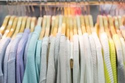 A close-up of cashmere sweaters on a clothing rack