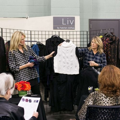 Clothing Reps showing a blouse to buyers at a trade show