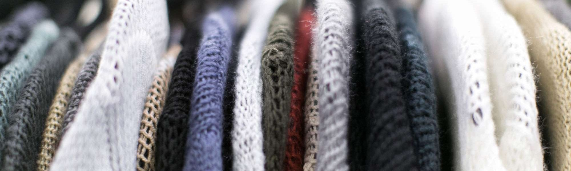 A close-up of sweaters on a clothing rack