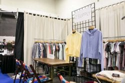 yellow and blue sweatshirts hand on a clothing rack at an apparel trade show