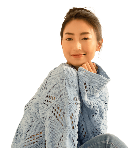 girl in a knit sweater smiling at the camera